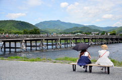Japanese women sit and looking view of Togetsukyo Bridge and Oi. River at Arashiyama on July 12, 2015 in Kyoto, Japan Stock Photos