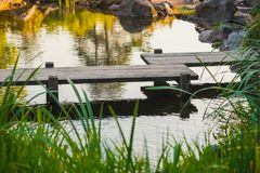 Japanese wooden bridge over pond. In a garden with thick green grass in the foreground Stock Photo