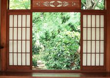 Japanese wooden entrance door background with garden outside royalty free stock photography