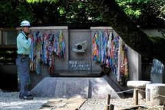 A japanese worker is standing beside the CND Peace monument at the Ueno Park in Tokyo royalty free stock images
