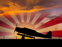 Japanese World War 2. Torpedo bomber sihlouette on an aircraft carrier at dawn with a rising sun naval flag in the background Stock Photo
