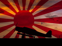 Japanese World War 2. Torpedo bomber sihlouette on an aircraft carrier at dawn with a rising sun naval flag in the background Royalty Free Stock Images