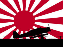 Japanese World War 2. Torpedo bomber sihlouette on an aircraft carrier with a 'Rising Sun' naval flag background Royalty Free Stock Photos