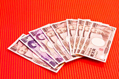 Japanese yen notes on red Stock Images
