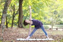 Japanewe woman doing yoga triangle pose Stock Image