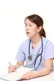 Japanische Ärztin mit Krankengeschichte spricht mit ihrem Patienten Lizenzfreie Stockfotografie