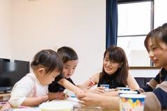 Japanische andere Mutter, die Lebensmittelpartei mit Kindern zu Hause hat Lizenzfreie Stockfotografie