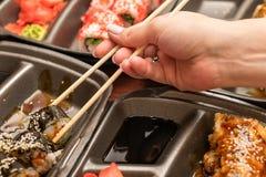 Japanische asiatische Küchemeeresfrüchtesushi und -rollen, in den Krabben des Mädchens Handund in den Fischen stockfotografie