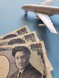 japanische Banknoten, weißes Plastikflugzeug und blauer Hintergrund lizenzfreie stockfotografie