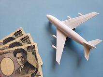 japanische Banknoten, weißes Plastikflugzeug und blauer Hintergrund lizenzfreie stockbilder