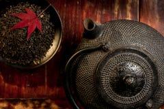 Japanische Eisenteekanne und Haufen von Teeblättern von der Spitze. Stockfotografie