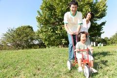 Japanische Familie, die im Park spielt Stockfoto