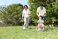 Japanische Familie, die im Park spielt Stockbild