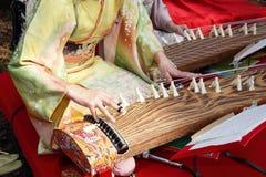Japanische Frau, die das traditionelle Instrument spielt Lizenzfreie Stockfotografie