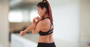 Japanische Frau, die an der Turnhalle ausdehnt lizenzfreie stockfotos
