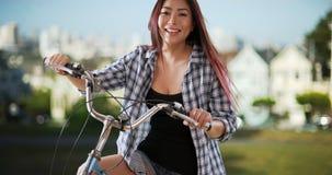 Japanische Frau, die mit ihrem Fahrrad am Park lächelt lizenzfreie stockfotos