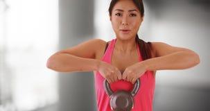 Japanische Frau, die mit kettlebell ausarbeitet stockbild