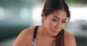 Japanische Frau, die nachdem dem Ausarbeiten stillsteht stockfoto