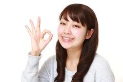 Japanische Frau, die perfektes Zeichen zeigt Lizenzfreies Stockfoto