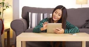 Japanische Frau, die Tablette auf Couchtisch verwendet Stockfotos