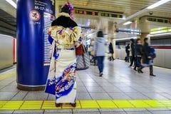 Japanische Frau in einem traditionellen Winter Kimonokleid an einer U-Bahnstation Lizenzfreie Stockbilder