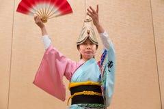 Japanische Frau im japanischen Trachtenkleid durchführendes lokales DA Stockfotografie