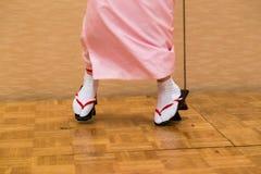 Japanische Frauen, die in traditioanl Kleid und in geta-Schuhe tanzen lizenzfreie stockbilder