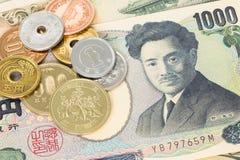 Japanische Geldyenbanknote und -münzen Stockbild