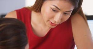 Japanische Geschäftsfrau, die mit hispanischem Kollegen spricht lizenzfreie stockfotos