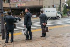 Japanische Geschäftsmänner warten durch Kreuzungszebrastreifen in Osaka, Japan stockbild