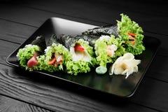 Japanische geschmackvolle temaki Sushi stellten auf schwarzen Hintergrund ein Stockfoto