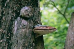 Japanische hölzerne Carvings von einem Buddha in einem Tokyo-Wald mit einem Pilz und Münzen Stockbilder