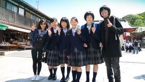 Japanische junge Schulmädchen, die mit Touristen aufwerfen Stockfotografie