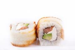 Japanische Küche, Sushi eingestellt: rollen Sie mit Aal, Lachs, Frischkäse, Avocado, teriyaki Soße, indischer Sesam auf einem wei Stockfoto