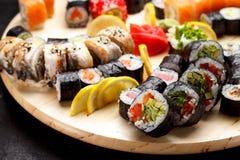 Japanische Küche Sushi stellten auf ein rundes hölzernes Brett über schwarzem Beton ein Stockbilder