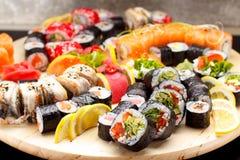 Japanische Küche Sushi stellten auf ein rundes hölzernes Brett über schwarzem Beton ein Stockfotos