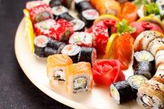 Japanische Küche Sushi stellten auf ein rundes hölzernes Brett über schwarzem Beton ein Stockfoto
