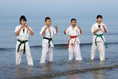 Japanische Karatejungen und -mädchen am Strand Lizenzfreies Stockfoto
