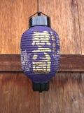 Japanische Laterne auf hölzerner Wand Stockbild