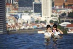 Japanische Mädchen, die selfies im Swimmingpool nehmen lizenzfreie stockfotos