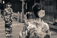 Japanische Mädchen in traditionellen Sommer yukatas, die Fotos von einander mit letztem Technologiemobiltelefon in Japan machen stockfoto