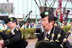 Japanische Männer, welche die Dudelsäcke für St Patrick Tagesfeiern spielen Lizenzfreie Stockfotografie