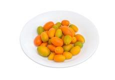 Japanische Orangen auf weißem Teller auf einem hellen Hintergrund Lizenzfreies Stockbild
