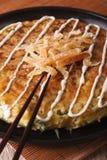 Japanische Pizza: okonomiyaki auf einer Platte und Essstäbchen vertikal Lizenzfreie Stockfotografie