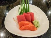 Japanische rohe Fische auf weißer Platten- und schwarzer Marmorierungtabelle Alias Sashimi Lizenzfreie Stockfotos