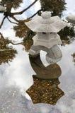 Japanische Steinlampe mit Reflexion stockfotos