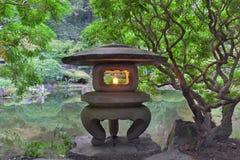 Japanische Steinlaterne durch den Nebenfluss Stockbild