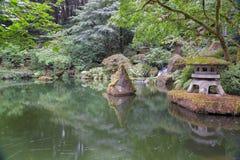 Japanische Steinlaterne durch den Teich Lizenzfreies Stockfoto