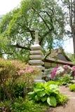 Japanische Steinstatue und altes Teehaus Stockfotografie