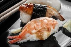 Japanische Sushi gemacht vom Reis und vom Wolfsbarsch, Garnele und geräucherter Aal mit Essstäbchen auf einem Schwarzblech Stockfotografie